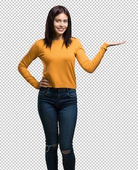 Młoda ładna kobieta trzyma coś rękami, pokazuje produkt, uśmiechnięta i wesoła, oferująca wyimaginowany przedmiot