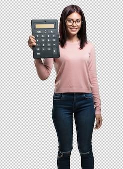 Młoda ładna kobieta wesoła i uśmiechnięta, trzymając kalkulator