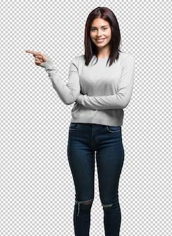 Młoda ładna kobieta wskazuje na bok, uśmiecha się zaskoczona, prezentując coś naturalnego i swobodnego