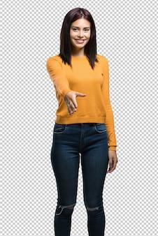 Młoda ładna kobieta wyciąga rękę, by kogoś przywitać lub gestem pomaga, szczęśliwa i podekscytowana