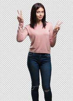 Młoda ładna kobieta zabawna i szczęśliwa, pozytywna i naturalna, robi gest zwycięstwa, pokoju koncepcja