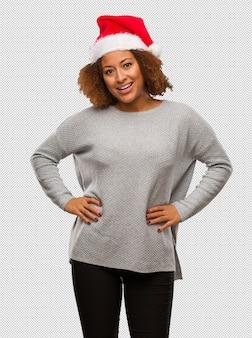 Młoda murzynka jest ubranym santa kapelusz z rękami na biodrach