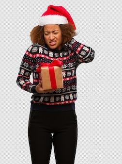 Młoda murzynka trzyma prezent w święto bożęgo narodzenia cierpi szyja ból