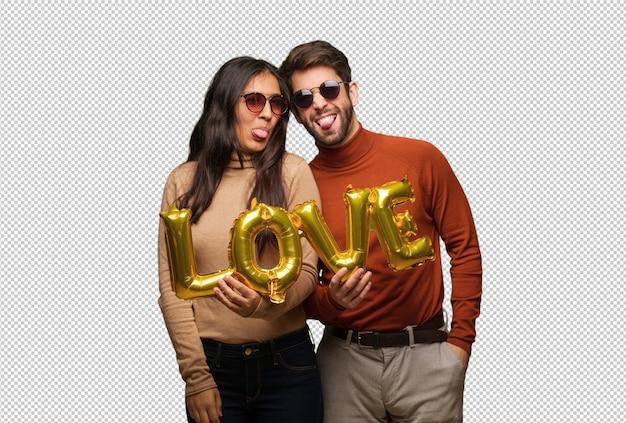 Młoda para w dzień valentines funnny i przyjazny pokazujący język