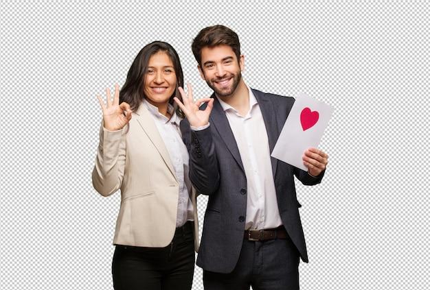 Młoda para w walentynki wesoły i pewny siebie, wykonując ok gest