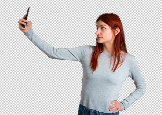 Młoda rudzielec dziewczyna bierze selfie z wiszącą ozdobą