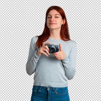 Młoda rudzielec dziewczyna trzyma kamerę