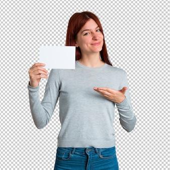 Młoda rudzielec dziewczyna trzyma pustego białego plakat dla wkłada pojęcie