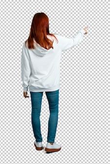 Młoda rudzielec dziewczyna w miastowej białej bluzie z szkłami wskazuje z powrotem