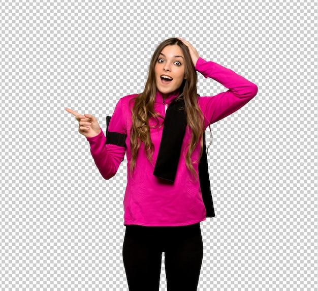 Młoda sport kobieta wskazuje palec strona i przedstawia produkt