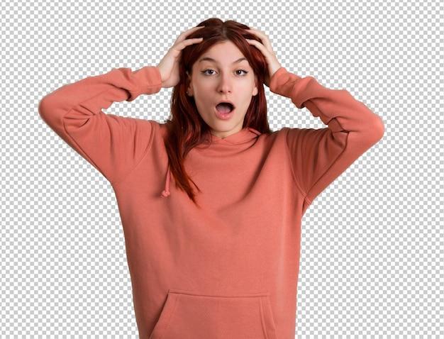 Młode rude dziewczyny z różową bluzą z niespodzianką i zszokowany wyraz twarzy