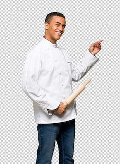 Młody afro amerykański szef kuchni człowiek palcem wskazującym na stronie w pozycji bocznej
