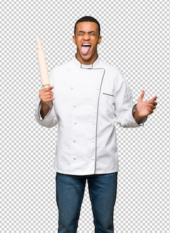 Młody afro amerykański szef kuchni mężczyzna pokazuje jęzor przy kamerą ma śmiesznego spojrzenie