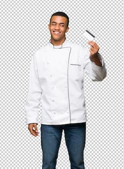 Młody afro amerykański szef kuchni mężczyzna trzyma kredytową kartę i główkowanie