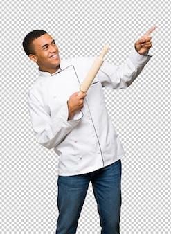 Młody afro amerykański szef kuchni mężczyzna wskazuje z palcem wskazującym i przyglądającym up