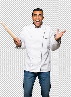 Młody afro amerykański szef kuchni mężczyzna z niespodzianką i szokującym wyrazem twarzy