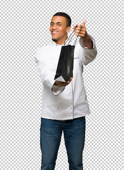 Młody afro amerykański szefa kuchni mężczyzna trzyma mnóstwo torba na zakupy