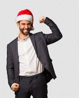 Młody biznesowy mężczyzna jest ubranym santa kapelusz który no oddaje