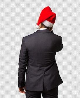 Młody biznesowy mężczyzna jest ubranym santa kapelusz od behind myśleć o coś