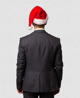 Młody biznesowy mężczyzna jest ubranym santa kapelusz od behind, przyglądającego z powrotem