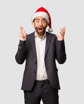Młody biznesowy mężczyzna jest ubranym santa kapelusz świętuje zwycięstwo lub sukces