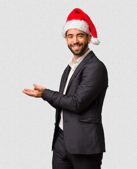 Młody biznesowy mężczyzna jest ubranym santa kapeluszowego mienia coś z rękami