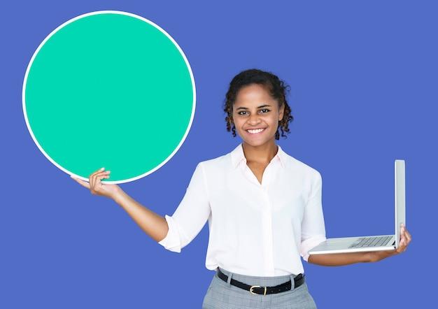 Młody bizneswoman trzyma pustego okrąg i laptop