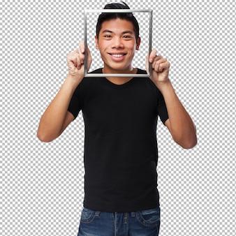 Młody chiński mężczyzna patrzeje przez ramy