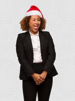 Młody czarny bizneswoman jest ubranym boże narodzenie santa kapeluszowego funnny i życzliwego pokazuje jęzor