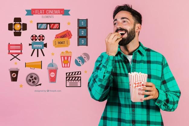 Młody człowiek jedzenie popcornu obok elementów kina