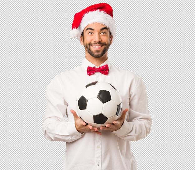 Młody człowiek jest ubranym santa claus kapelusz na dniu bożego narodzenia