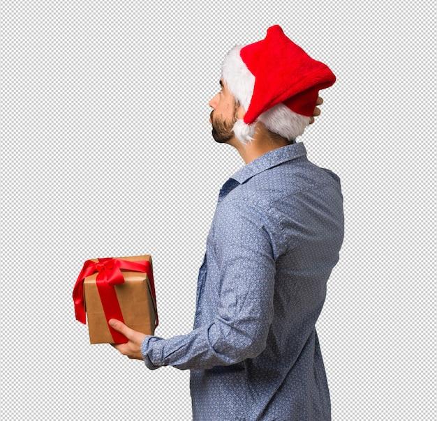 Młody człowiek jest ubranym santa kapelusz od behind myśleć o coś