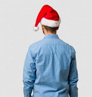 Młody człowiek ma na sobie kapelusz santa z tyłu, patrząc wstecz