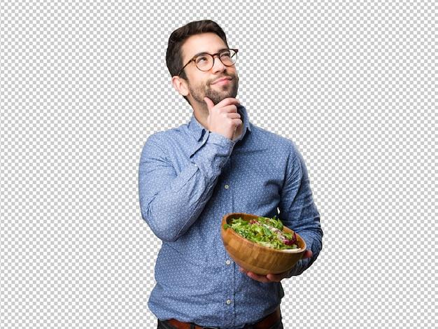 Młody człowiek myśli i trzyma sałatkę