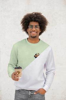 Młody człowiek pije kawę z kapturem