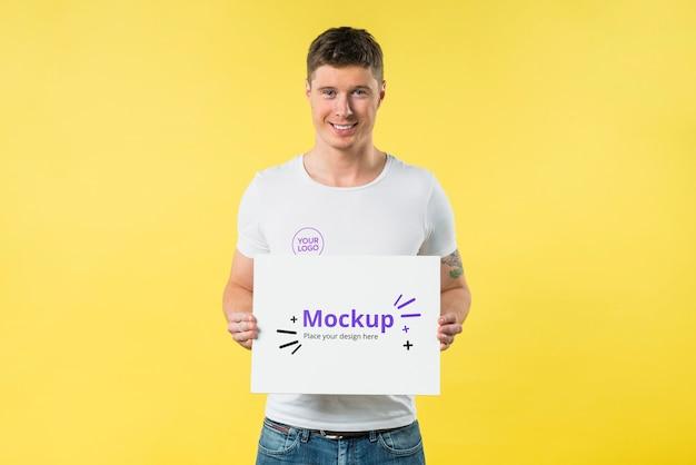 Młody człowiek stojący i trzymając makiety widok z przodu