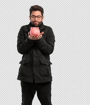 Młody człowiek trzyma piggie bank