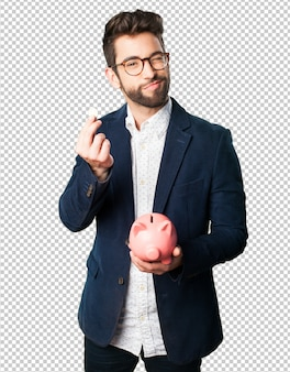 Młody człowiek trzyma prosiątko banka