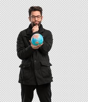 Młody człowiek trzyma światową kulę ziemską