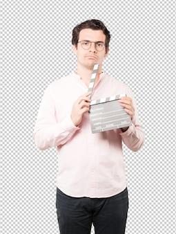Młody człowiek używa clapperboard