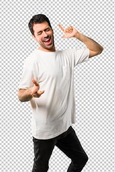 Młody człowiek z białą koszulę cieszyć się tańcem podczas słuchania muzyki na imprezie