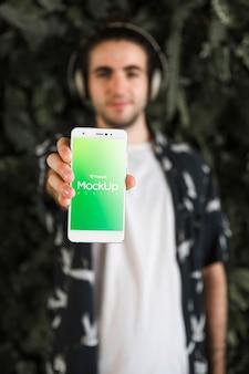 Młody człowiek z smartphone makietą