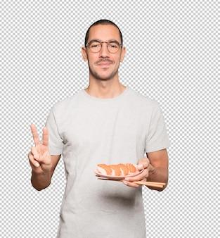 Młody człowiek za pomocą pałeczek do jedzenia sushi