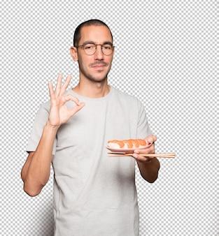 Młody Człowiek Za Pomocą Pałeczek Do Jedzenia Sushi Premium Psd