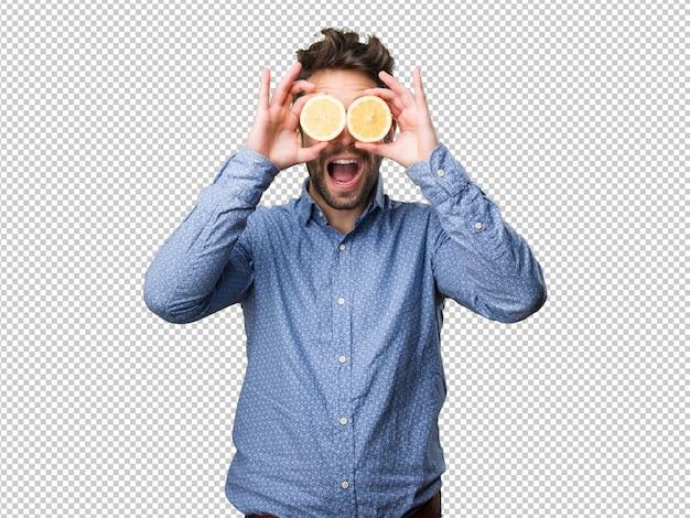 Młody człowiek zakrywa jego oczy z cytrynami