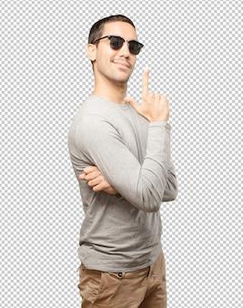 Młody mężczyzna ma na sobie okulary słoneczne i gesty