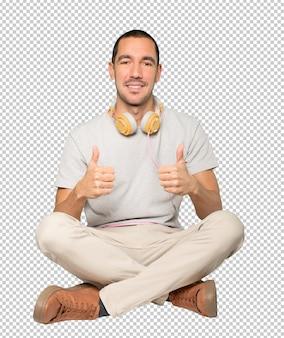 Młody mężczyzna w pozycji siedzącej z dobrym gestem