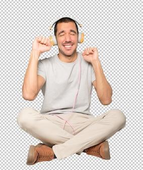 Młody mężczyzna w pozycji siedzącej z gestem celebracji