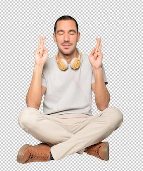 Młody mężczyzna w pozycji siedzącej z gestem skrzyżowanych palców