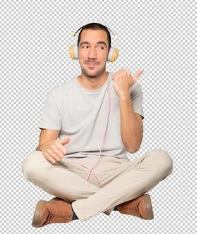 Młody mężczyzna w pozycji siedzącej z palcem wskazującym gest